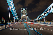 Cars drive past in a blur of motion at night atop the Tower Bridge in London, England.