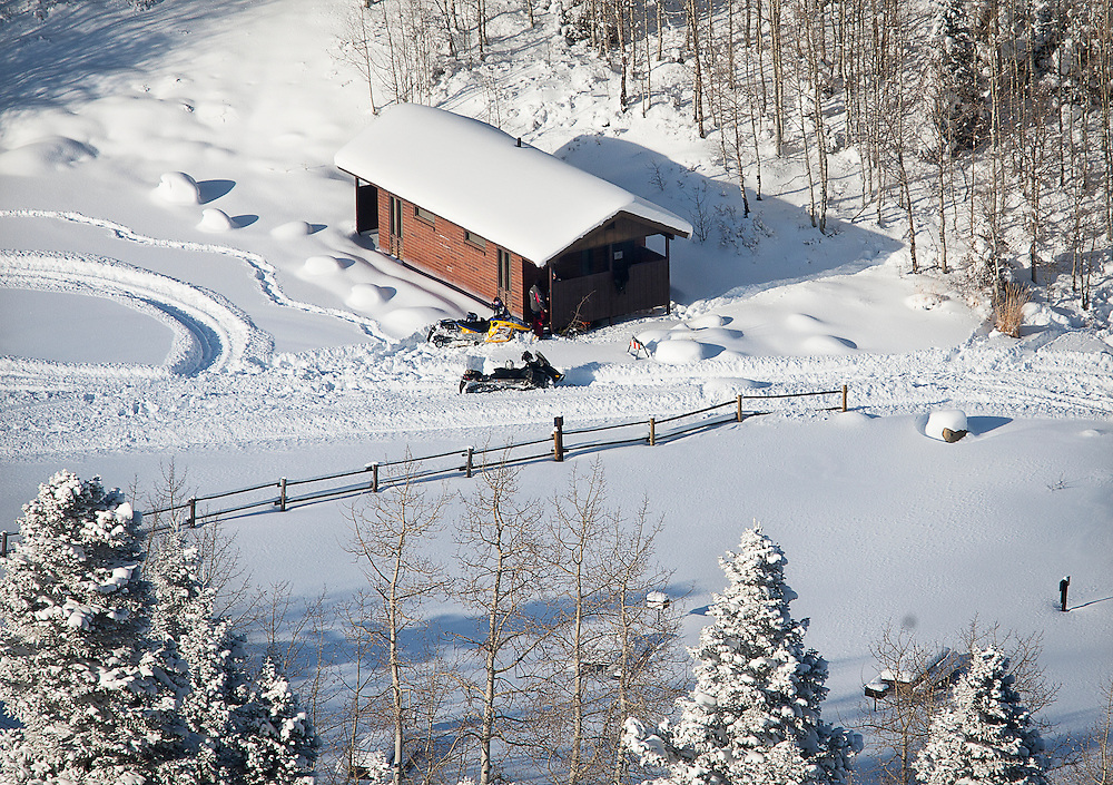 Snowmobiles parked outside a cabin near where a snowmobiler broke through the ice attempting to cross Payson Lake, Wednesday, Dec. 19, 2012