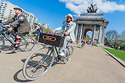 "Reaching Hyde Park Corner. The Tweed Run 2015 - it's 7th annual British public bicycle ride through London's historic streets, with a prerequisite that participants are dressed in their best tweed cycling attire. There are also plenty of handle bar moustaches, penny farthings and Union Jacks. ""Guests can expect a leisurely day cycling, stopping at some of London's most iconic landmarks to enjoy a spot of tea, a picnic in the park and finally a jolly good knees-up in a beautiful art-deco ballroom for the Tweed Run closing ceremony. Starting at Trafalgar Square, the cyclists then embarked on a 12 mile scenic ride through London, stopping at traditional spots."