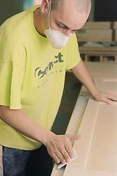 Cabinet maker sanding down blanket box using sand paper,