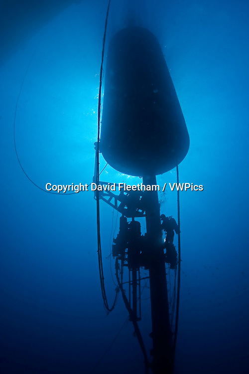 A diver (MR) works on a massive wave energy buoy off Kaneoho Bay, Oahu.  The 40-kW experimental buoy, employs the bobbing motion of the buoy to drive an electrical generator, that then sends power to the island via underwater cable, Hawaii.  The divers barge is anchored above.