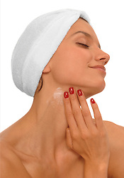 Beautiful, young woman wearing spa turban, applying lotion to her neck on a white background