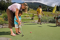 Mom and son play a round of mini-golf at the Adventure Zone, Blackcomb Mountain, Whistler, BC Canada.