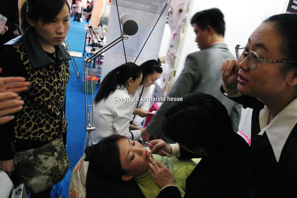 BEIJING, 22. October 2004 : potential customers (L) talk to a beauty expert (R) while a woman gets facial treatment by a professional at the International Beauty Week in Beijing, October 22, 2004, in China. Beauty business is booming in China. Sales in beauty related businesses and products are worth more than 7 billion USD last year.      ..Whereas in Mao Zedong's China, even pigtails were seen as a sign of vanity (and had to be cut off) , nowadays, urban Chinese women seek about every means in order to distinguish themselves from the masses.  This year Beijing will organize the worl'd first beauty pageant for women had had plastic surgery in early December...
