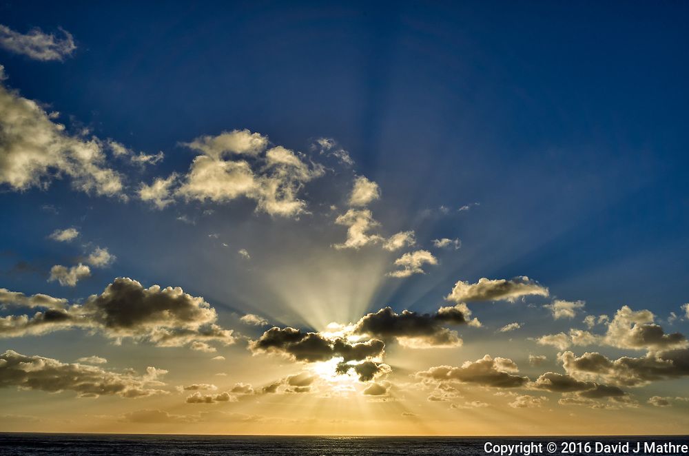 Morning sun and clouds with Crepuscular rays (God's rays) from the deck of the MV World Odyssey while traveling across the Pacific Ocean. Image taken with a Leica T camera and 23 mm f/2 lens (ISO 100, 23 mm, f/14, 1/500 sec). Raw image processed with Capture One Pro (including correction of white-balance).
