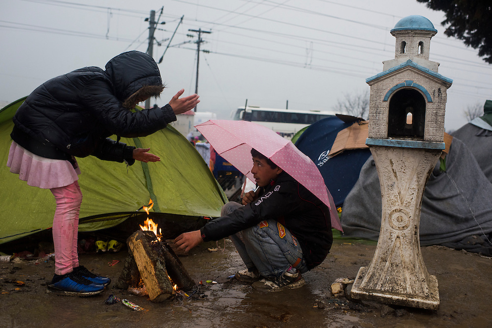 Young refugees huddle around a fire next to a small Greek shrine, called a Kandylakia, at a refugee camp on the Macedonian (FYROM) border on March 9, 2016 in Idomeni, Greece.