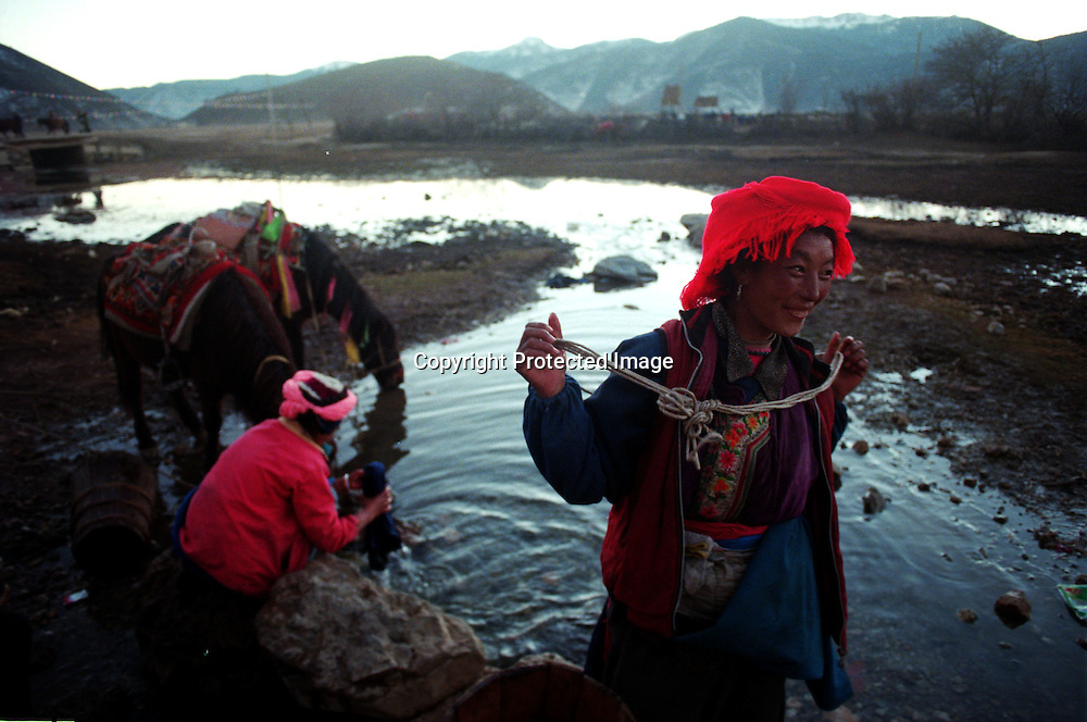 "ZHONGDIAN COUNTY, DECEMBER 19, 2000: Tibetan Kampa nomads wash their clothes and water their ponies at a spring at the end of the day, Yunnan province , December 19, 2000..Mt. Meili is the highest peak in Yunnan province and according to supporters from Deqin county, it's a ""proof"" that the 'real"" Shangri-La is located in deqin county. The fictuous Mt. Karakal which is described in James Hilton's Lost Horizon, alledgedly is modelled on Mt. Meili in Yunnan province.."