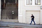 Een vrouw loopt bellend over een van de heuvels in San Francisco. De Amerikaanse stad San Francisco aan de westkust is een van de grootste steden in Amerika en kenmerkt zich door de steile heuvels in de stad.<br /> <br /> A woman walks a hill in San Francisco. The US city of San Francisco on the west coast is one of the largest cities in America and is characterized by the steep hills in the city.