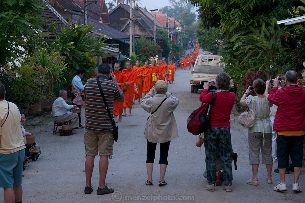 Luang Prabang, Laos. Wat Xieng Thong Buddhist temple complex. Tourists photographing tak bat. Every morning at dawn, Buddhist monks walk down the streets collecting food alms from devout, kneeling Bhddhists, and some tourists. They then return to their temples, or wats, and eat together. This procession is called Tak Bat, or Making Merit.