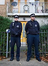 ©  London News Pictures. 23/11/2013. London, UK. Police guard the entrance to a  flat on Peckford Place, South London, which has been revealed as the location where three women where held captive as slaves for 30 years.  The alleged captors were arrested and questioned but have since been released on bail. Photo credit : Ben Cawthra/LNP