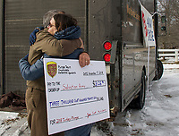 Mark Emery gets a heartfelt hug from Nora McNeil of the Salvation Army for the Team UPS dedication in continuing the Turkey Plunge tradition on Saturday morning at Bartlett Beach.
