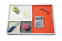 Tray with green apple, calculator, eyewear and other office supplies