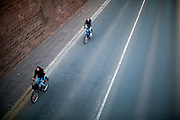 """Germany banned gatherings of more than 2 people called """"social distancing"""" because of the coronavirus. Cyclists at the shore of river Main in Frankfurt which is very empty on a - normally very busy - Thursday evening."""