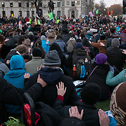 Thousands of Extinction Rebellion activists took over 5 bridges in Central London and blocked them for the day, November 17 2018, Central London, United Kingdom. People are encouraged to put a hand on each other and told that every action has an impact. A final vigil and multi-faith prayer service finished the day of rebellion in Parliamnet Square. Around 11am people on all bridges sat down in the road and blocked traffic from coming through and stayed till late afternoon. The actvists believe that the government is not doing enough to avoid catastrophic climate change and they demand the government take radical action to save future generations and the planet. Many are willing to be arrested peacefully protesting and up to 80 were arrested on the day. Extinction Rebellion is a grass root climate change group started in 2018 and has gained a huge following of people commited to peaceful protests and who ready to be arrested. Their major concern is that the world is facing catastropohic climate change and they want the British government to act now to save future generations.
