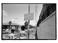 Two ultra-orthodox Jewish men walk past the street sign of the prodominantly Arab neighbourhood Sheikh Jarrah, which is slowly taken over by Jewish settlers who buy up houses in the area.