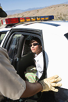 Police man with young woman in police car