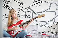 Full-length portrait of teenage girl playing guitar in bedroom