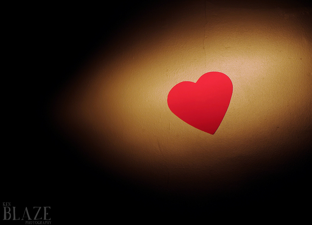 Foam heart on taped to wall photographed with a flashlight as the main light source.