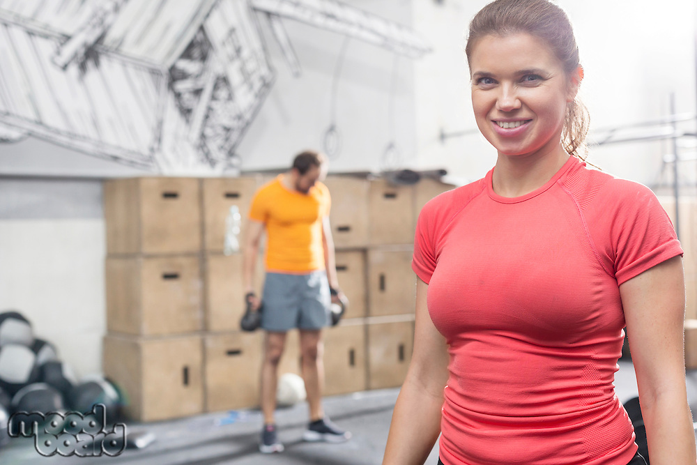 Portrait of happy woman standing in crossfit gym