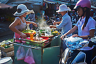 Market vendors serve streetfood from their cart to a waiting customer, Ho Chi Minh City, Vietnam, Southeast Asia