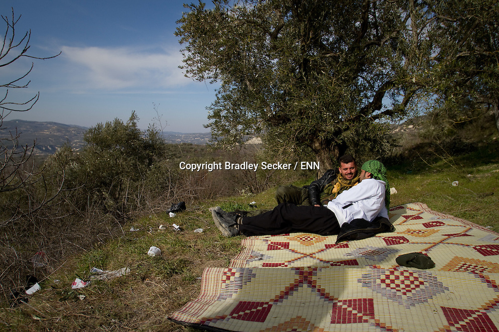 Soldiers from the Free Syrian Army relax under a tree between guarding duties. Al Janoudiyah, Syria