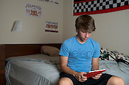 Alex Lee aka #AlexFromTarget plays with his new iPad he received from Ellen DeGeneres in his room on November 10, 2014 in Frisco, Texas. (Cooper Neill for The New York Times)