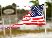 A U.S. flag shredded by Hurricane Wilma flies with the completely flooded town of Everglades City, Florida in the background after Hurricane Wilma hit October 24, 2005. Everglades City took a direct hit from the storm as it came ashore.