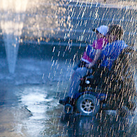 Two people in a motorized wheelchair taking a ride htorugh a public interactive fountain in Vancouver, Canada.