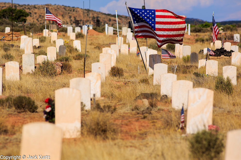 12 JULY 2012 - WINDOW ROCK, AZ:   American flags on graves in the Navajo Veterans' Cemetery. More than 300 Navajo veterans are buried in the Veterans' Memorial Cemetery north of Window Rock, AZ, on BIA Highway 12. The cemetery is in the windswept high desert. Members of the military killed overseas are returned to the reservation for burial. The tribe has set aside 10 acres in Chinle, in the center of the reservation, but that site is awaiting funding from Washington.     PHOTO BY JACK KURTZ
