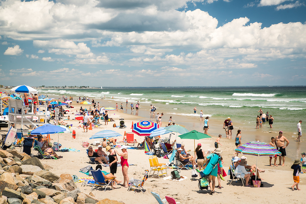 A perfect beach day on Ogunquit Beach brings out the crowds with bathing suits and beach umbrellas.