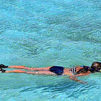Woman Snorkeling in Lagoon at Half Moon Cay, Bahamas <br /> One of the many fun activities on Half Moon Cay is snorkeling.  After renting equipment from one of three Water Sports Centers, you can enjoy your swim in the shallow waters near the Welcome Center or thrill at seeing southern stingrays at the Stingray Adventure Cove.  If you are an experienced snorkeler, then walk to the other end of the beach where you can explore exquisite coral in 75 to 100 feet of water.