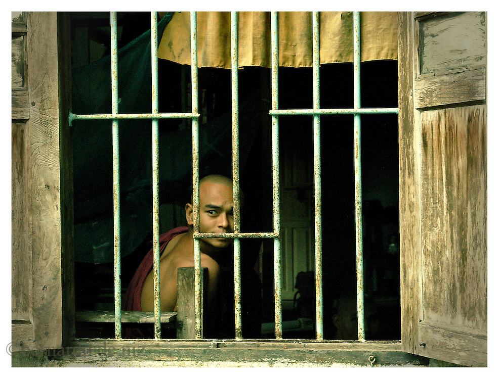A monk peers through the bars of his cell in one of the old monasteries of Bago, the old Burmese capital Saturday, October 6, 2007. .Many monks in their twenties are now the target of the persecution and repression of the military dictatorship in Burma, after them took the streets to protest against them..Bago, Myanmar (Burma).
