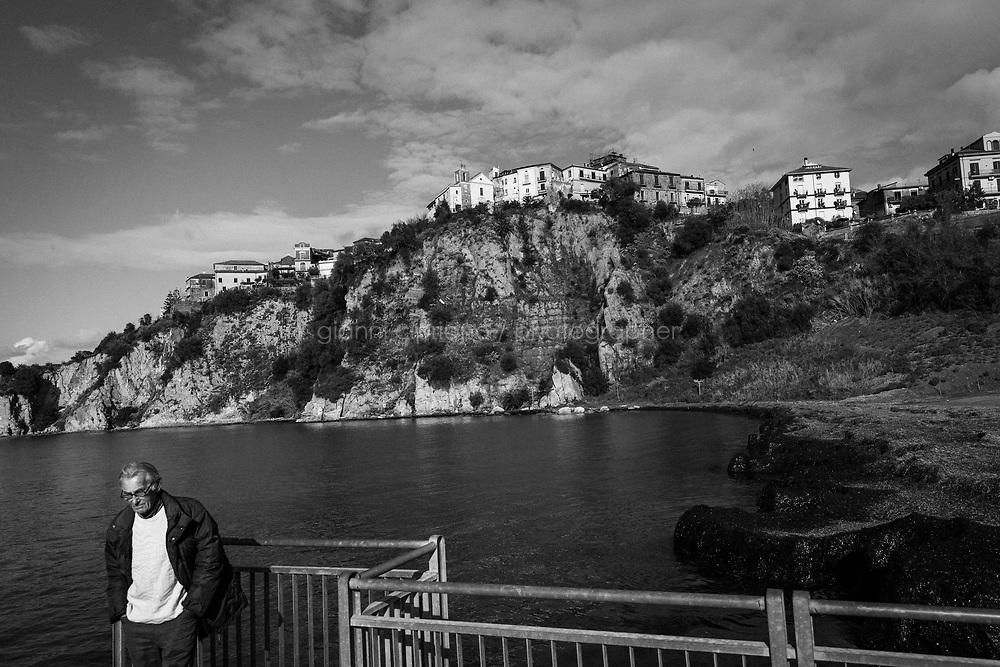 AGROPOLI (SA) - 4 FEBBRAIO 2018: Un uomo passeggio nel porto di Agropoli, città  amministrata dall'ex sindaco Franco Alfieri, ora candidato alla Camera dei Deputati nel collegio uninominale di Agropoli (Campania) il 4 febbraio 2018.<br /> <br /> Le elezioni politiche italiane del 2018 per il rinnovo dei due rami del Parlamento – il Senato della Repubblica e la Camera dei deputati – si terranno domenica 4 marzo 2018. Si voterà per l'elezione dei 630 deputati e dei 315 senatori elettivi della XVIII legislatura. Il voto sarà regolamentato dalla legge elettorale italiana del 2017, soprannominata Rosatellum bis, che troverà la sua prima applicazione<br /> <br /> ###<br /> <br /> AGROPOLI, ITALY - 4 FEBRUARY 2018: A man walks by the harbor of Agripoli, a city once governed by former mayor Franco Alfieri,  now chief of staff of the governor of the Campania region Vincenzo De Luca and running as a candidate for the Chamber of Deputies in the 2018 Italian General Elections , in Agropoli, Italy, on February 4th 2018.<br /> <br /> The 2018 Italian general election is due to be held on 4 March 2018 after the Italian Parliament was dissolved by President Sergio Mattarella on 28 December 2017.<br /> Voters will elect the 630 members of the Chamber of Deputies and the 315 elective members of the Senate of the Republic for the 18th legislature of the Republic of Italy, since 1948.