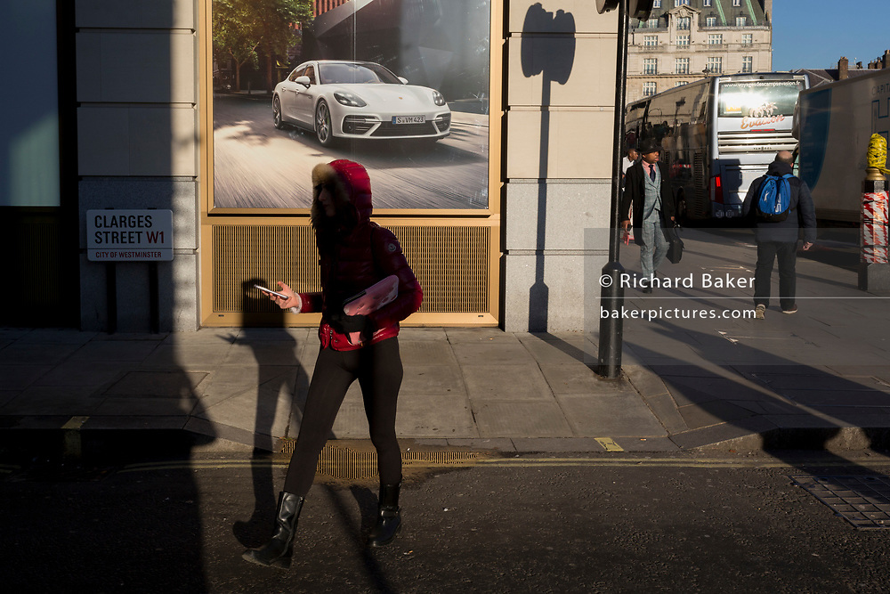 A lady carries her phone while walking past a Porsche luxury car ad where a new dealership is due to open on the corner of Clarges Street, and Piccadilly, W1, on 20th January 2020, in London, England.