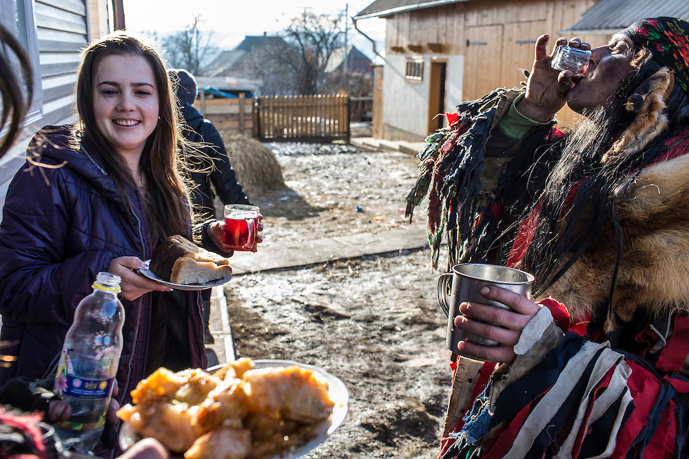 KRASNOILSK, UKRAINE - JANUARY 14: Villagers stop for a drink and a snack during the winter festival of Malanka on January 14, 2015 in Krasnoilsk, Ukraine. The holiday, which involves dressing in elaborate costumes and going from house to house as a group singing traditional songs, is celebrated on New Year's Day of the Orthodox calendar, a week after Orthodox Christmas. (Photo by Brendan Hoffman/Getty Images) *** Local Caption ***