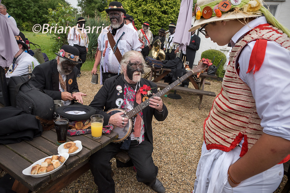 Thaxted Morris Weekend, Thaxted Essex England UK. 2-3 June 2018<br /> The 85th Meeting of the Member Clubs of the Morris Ring hosted by Thaxted Morris Men. Seen here the Silurian Side from Herefordshire outside the Farmhouse Inn at Monk Strret, Dunmow Essex on Saturday morning. Silurian banjo player, Bob Dodey, chatting to a young member of the Thaxted Morris side.