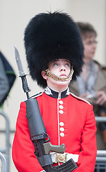 © Licensed to London News Pictures. 04/06/2014. Westminster, UK . A soldier looks up during the parade. Queen Elizabeth II being driven down The Mall in the new Diamond Jubilee State Coach to attend the State Opening of Parliament on June 4th 2014 in London. In a speech to Members of Parliament and Peers in The House of Lords, Queen Elizabeth II will officially open a new session of parliament, which will set out the government's agenda and legislation for the coming year.. Photo credit : Stephen Simpson/LNP