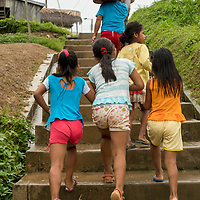 Young Peruvian girls walk up stairs with a fisherman in the village of San Francisco off of the Marañon River. Pacaya Samiria National Reserve, Upper Amazon, Peru.
