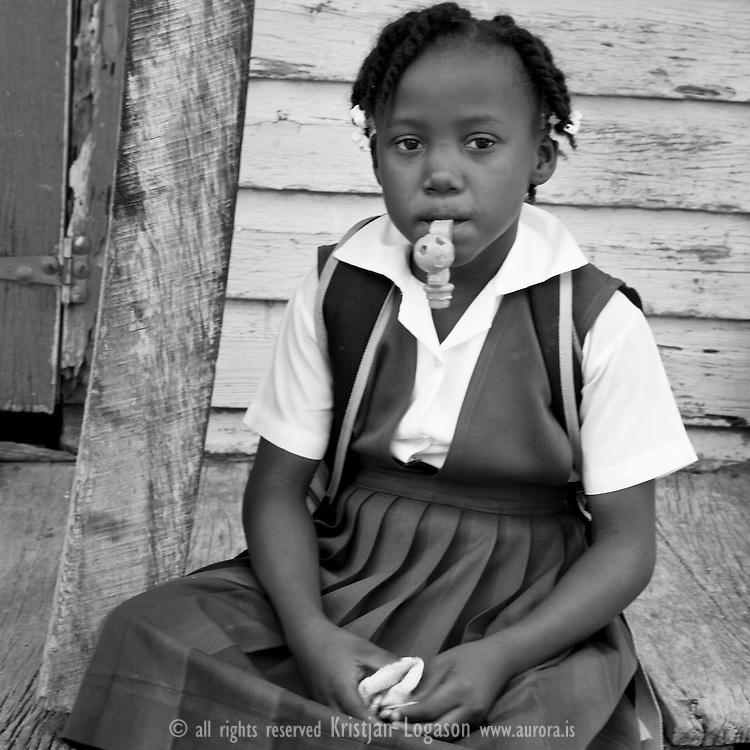 Young girl in Dangriga Belize coming home from School in here purple uniform