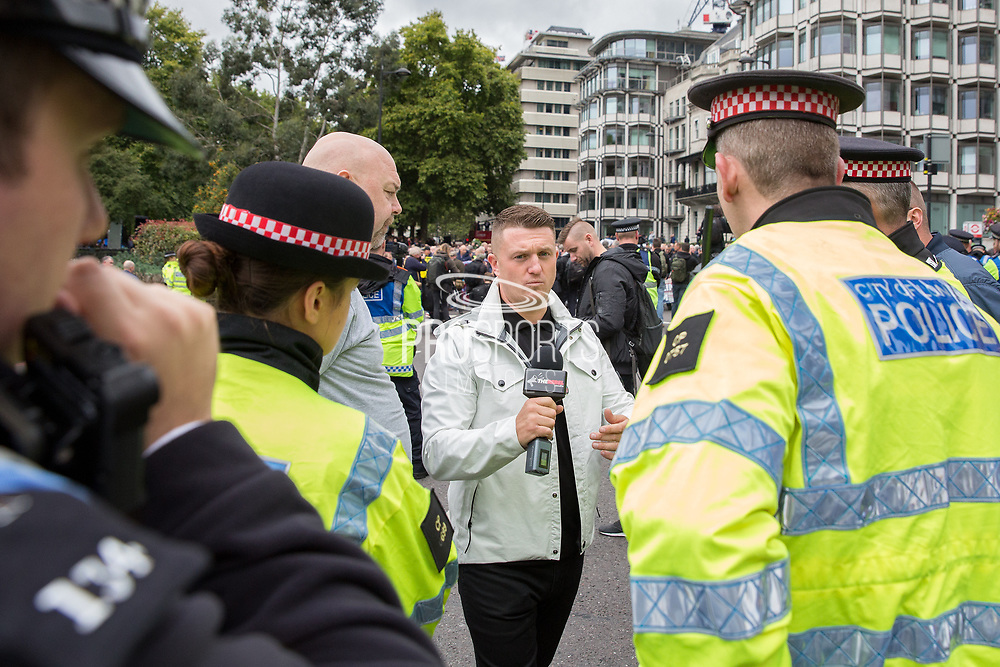 Tommy Robinson talks to the Police during the Football Lads Alliance march between Park Lane and Westminster Bridge, London on 7 October 2017. Photo by Phil Duncan.