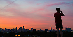 London, August 16 2017 . An early riser takes a picture of the city skyline as London wakes up to a glorious sunrise. © Paul Davey.