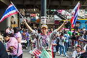 """09 DECEMBER 2013 - BANGKOK, THAILAND: Thai anti-government protestors rally on Silom Road in Bangkok before marching on Government House in Bangkok. Thai Prime Minister Yingluck Shinawatra announced she would dissolve the lower house of the Parliament and call new elections in the face of ongoing anti-government protests in Bangkok. Hundreds of thousands of people flocked to Government House, the office of the Prime Minister, Monday to celebrate the collapse of the government after Yingluck made her announcement. Former Deputy Prime Minister Suthep Thaugsuban, the organizer of the protests, said the protests would continue until the """"Thaksin influence is uprooted from Thailand."""" There were no reports of violence in the protests Monday.      PHOTO BY JACK KURTZ"""