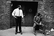 Two black guys, one wearing a 1940's suit. wapping, London 1982