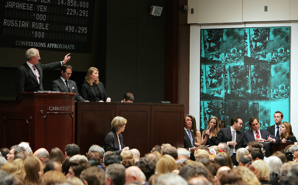 Andy Warhol's 'Green Car Crash (Green Burning Car I)' (seen at right) is auctioned by Christopher Burge (at podium) at Christie's auction house in New York, New York on 16 May 2007. The painting sold for a total of $71,720,000 (USD), a record for a Warhol, during an auction of post-war and contemporary art.
