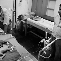 Dr. Yogesh Jain (left), records the progress of a newborn baby as the child's father looks on. The child had been treated for a hernia in a government hospital and the parents had brought him to the JSS hospital at Ganiyari for a second opinion. <br />