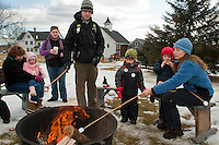 Eric and Emily Wolpin roast marshmallows over the firepit for their children Ben and Owen as they enjoy smores during the 2nd annual Winter Fest held Saturday at Prescott Farm Environmental Education Center in Gilford.  (Karen Bobotas/for the Laconia Daily Sun)