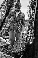 Fisherman mending commercial salmon seine net in Saint Paul Harbor, Kodiak Island, Alaska, summer