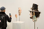 New York, NY - 5 May 2017. The opening day of the Frieze Art Fair, showcasing modern and contemporary art presented by galleries from around the world, on Randall's Island in New York City. A creepy mixed-media head of Abraham Lincoln by David Altmejd in the gallery of Xavier Hufkens appears to look at a man taking photos of another of Altmejd's sculptures.