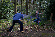 A father and his 7 year-old son use sticks to play a swordfighting game in local woods, on 23rd April 2017, in Wrington, North Somerset, England.