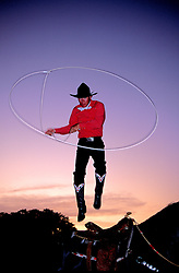 Bandera, Texas:  Cowboy Kevin Fitzpatrick leaps through his lasso at twilight, from the back of his horse.
